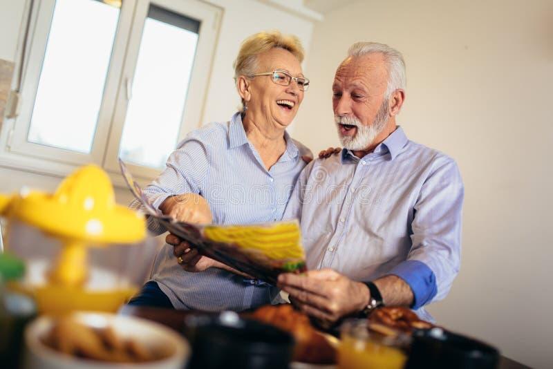 Journal âgé positif de lecture de couples à la maison image stock