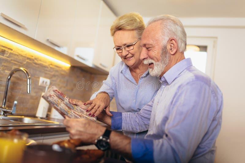 Journal affectueux âgé de lecture de couples à la maison images stock