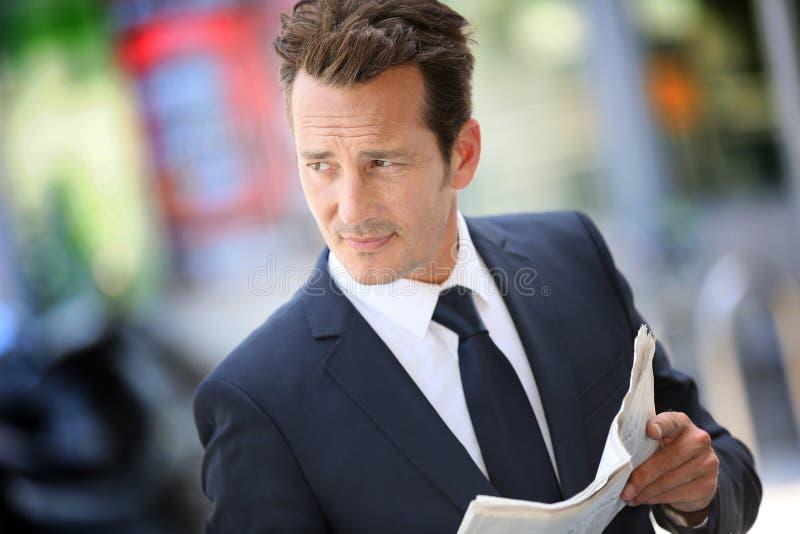 Journal beau de lecture d'homme d'affaires dans les rues image libre de droits