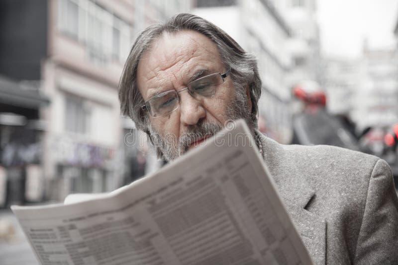 Journal de lecture d'homme supérieur dedans dehors photo stock