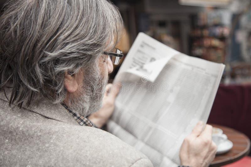 Journal de lecture d'homme supérieur dedans dehors photos stock