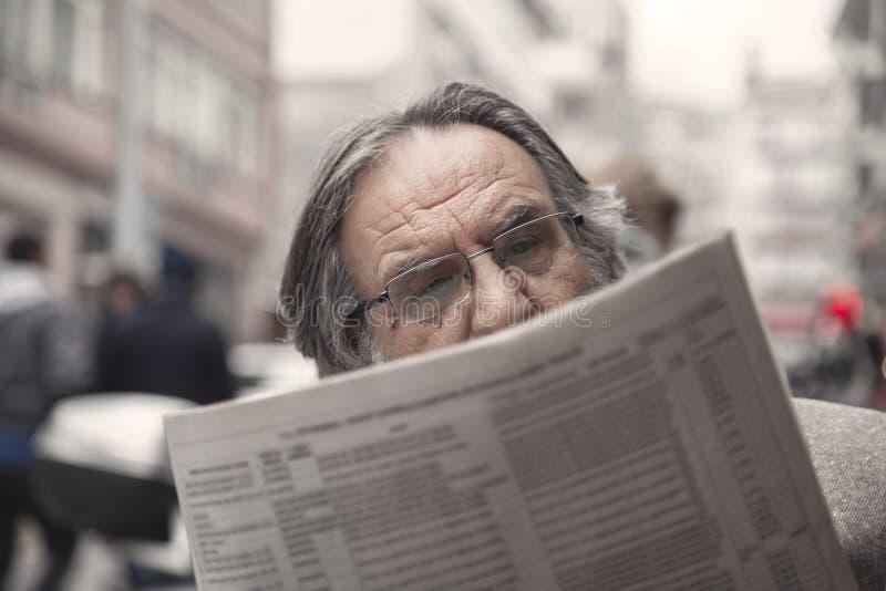 Journal de lecture d'homme supérieur dedans dehors photographie stock libre de droits