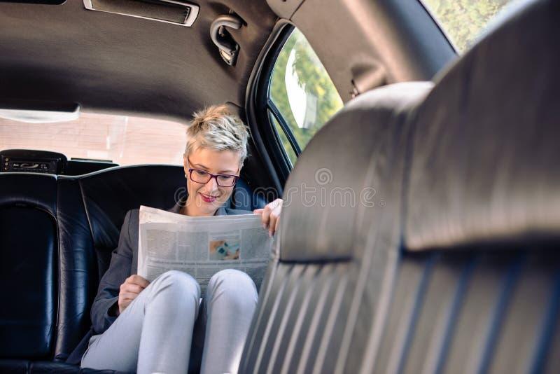 Journal de lecture de femme d'affaires dans la limousine images libres de droits