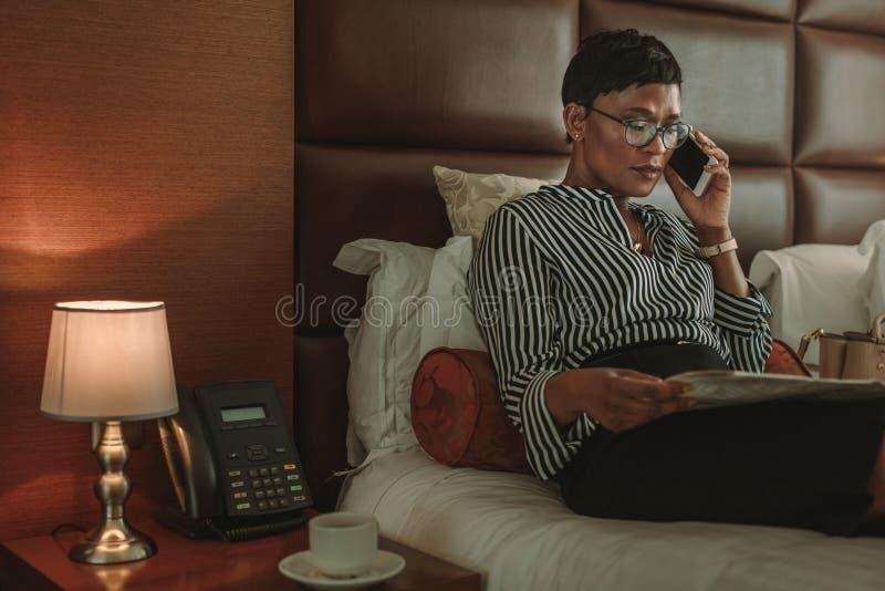 Journal de lecture de femme d'affaires et parler au téléphone portable dans chaud photo stock