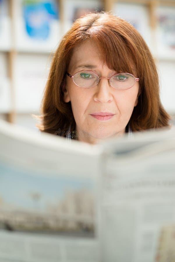 Journal du relevé de femme âgée dans la bibliothèque photos stock