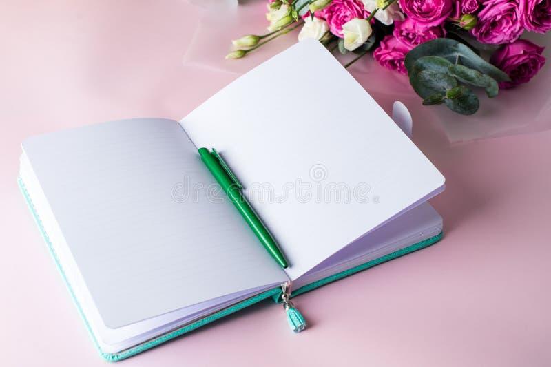 Journal intime de femme, stylo et belles fleurs sur la table rose avec le copysp photo libre de droits