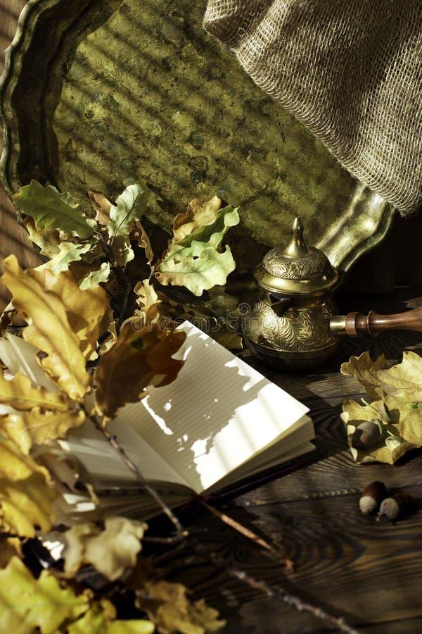 Journal intime, feuilles de chêne d'automne et pot de café turc sur un fond en bois Copiez l'espace confortable Concept d'automne images stock