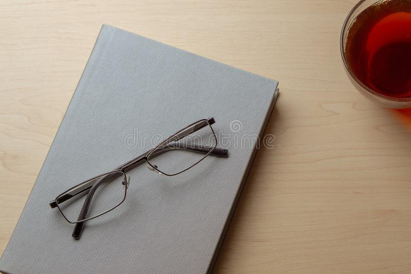 Journal intime gris, tasse de thé, et verres sur une table brune, vue supérieure Copiez l'espace photos stock