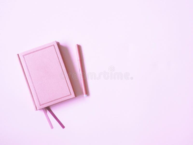 Journal intime rose avec un stylo sur un fond rose images stock