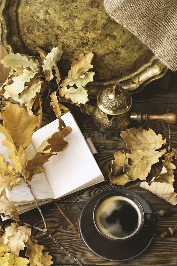 Journal intime, tasse de café chaud, feuilles de chêne d'automne, pot de café turc sur un fond en bois Copiez l'espace confortabl photos libres de droits