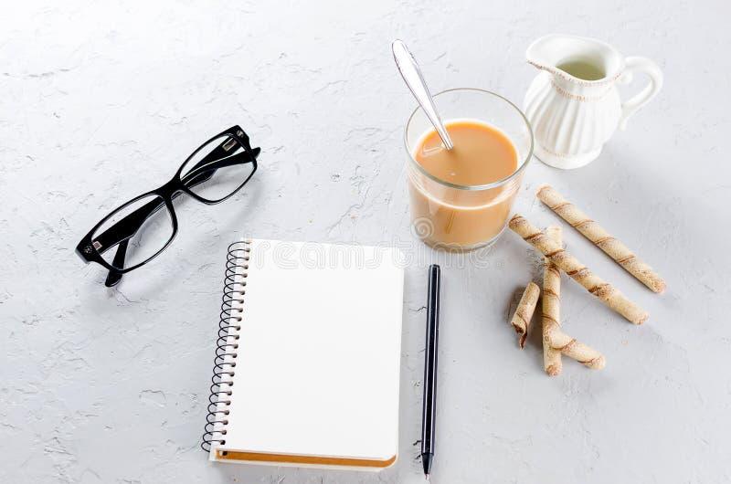 Journal intime vide, stylo, tasse de café et verres sur le fond gris photo libre de droits