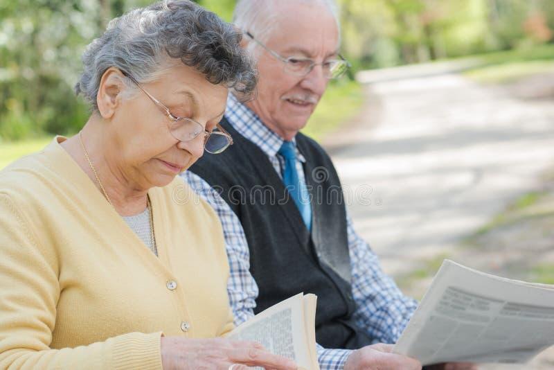Journal mûr heureux de lecture de couples dehors images stock