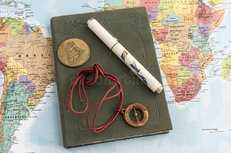 Journal with pen, talisman and coin on map. Green hard cover journal with pen, stringed compass talisman and coin on top of map displaying South American and stock photography