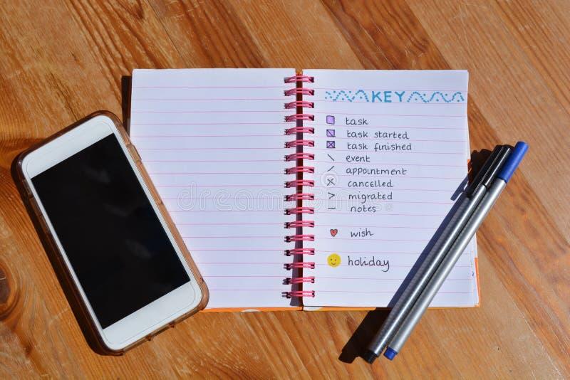 Journal, stylos et téléphone portable de balle sur le bureau photographie stock libre de droits