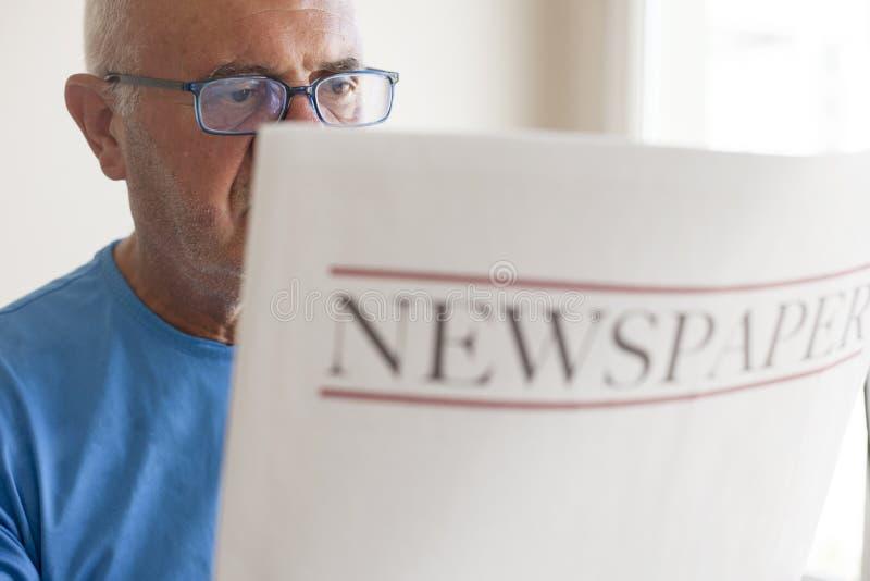 Journal supérieur de lecture de vieil homme photo stock