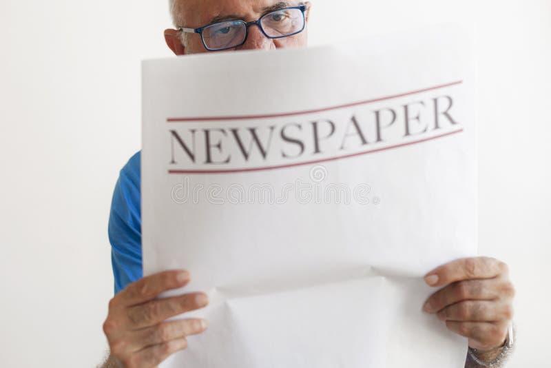 Journal supérieur de lecture de vieil homme image stock