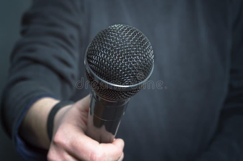 Journalist die toespraak met microfoon en hand gesturing concept voor gesprek maken stock afbeelding