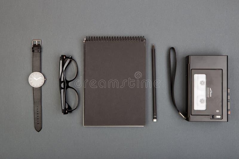 Journalist- eller bloggertabell - spirala tomma anteckningsbok, blyertspenna, bandspelare och exponeringsglas på grå bakgrund, bä arkivfoton
