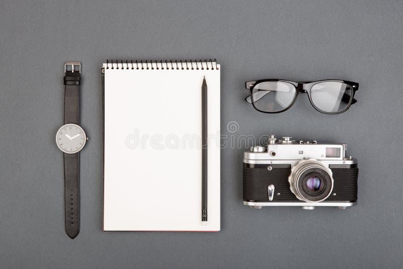 Journalist- eller bloggertabell - spirala tomma anteckningsbok, blyertspenna, kamera och exponeringsglas på grå bakgrund, bästa s royaltyfria foton
