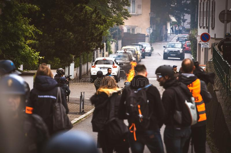 Journalist fire on Rue Rene Schickele during Yellow Vests protest. Strasbourg, France - Apr 28, 2019: Silhouettes of Press media journalists with helmets on rue royalty free stock image