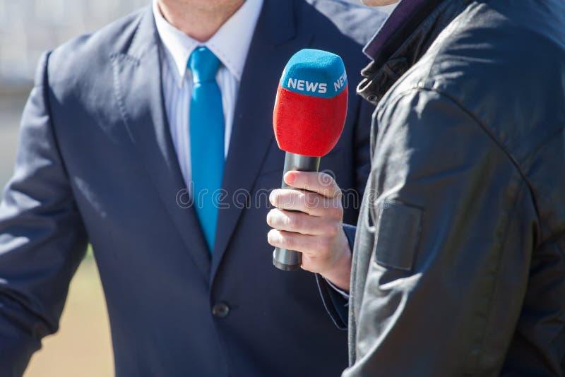 Journalist med att intervjua för mikrofon arkivbilder
