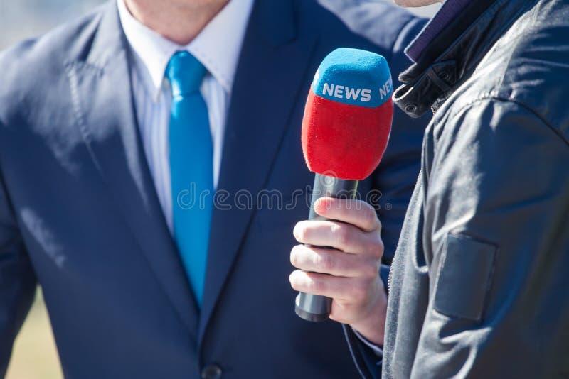 Journalist med att intervjua för mikrofon fotografering för bildbyråer