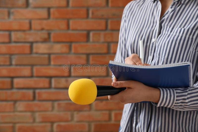 Journalist with microphone and notebook near wall, closeup stock image