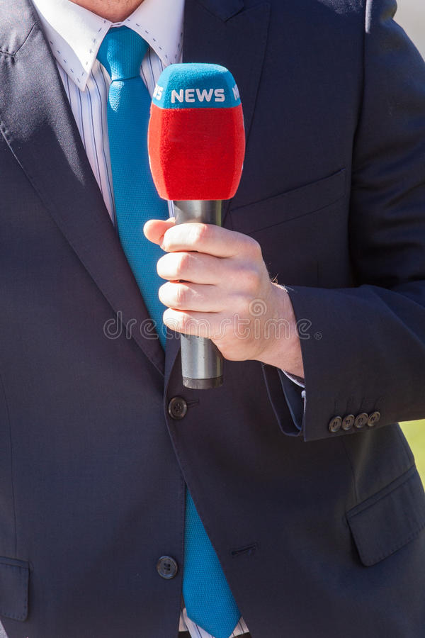 Journalist with microphone reporting. News journalist with microphone reporting royalty free stock images