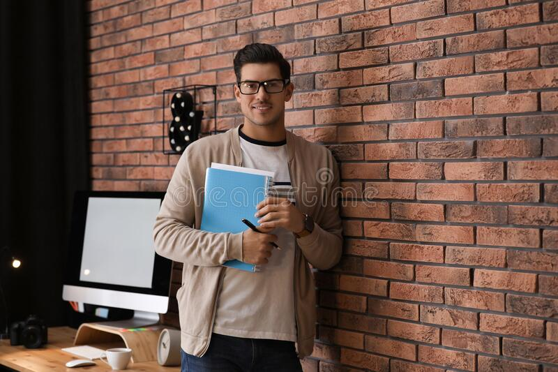Journalist with notebook near wall in office stock photos