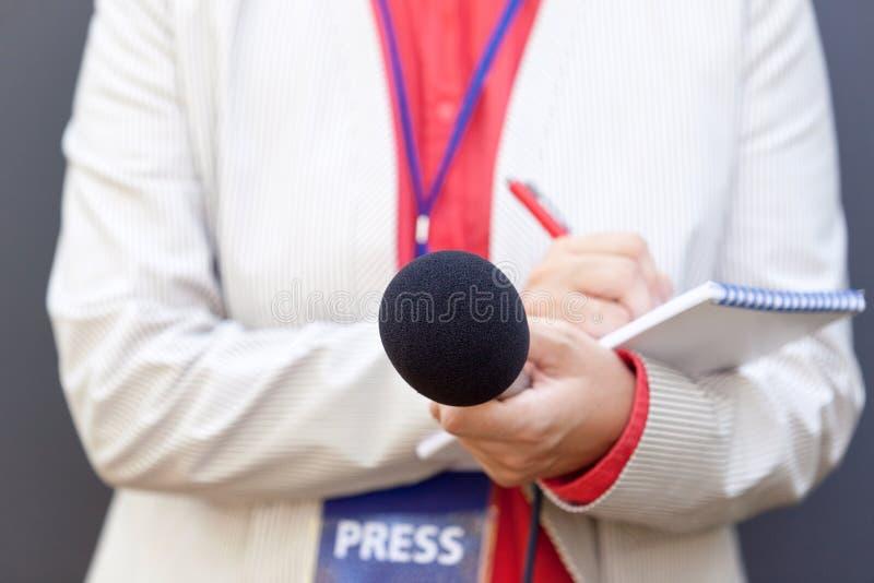 Journalista fêmea na conferência de imprensa, microfone da terra arrendada, escrevendo notas foto de stock royalty free