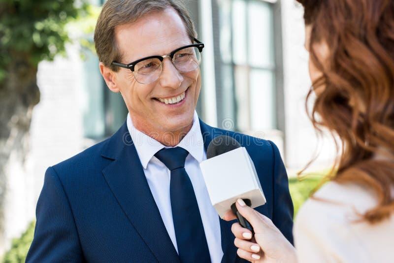 journalista fêmea que toma a entrevista com o homem de negócios maduro alegre fotografia de stock