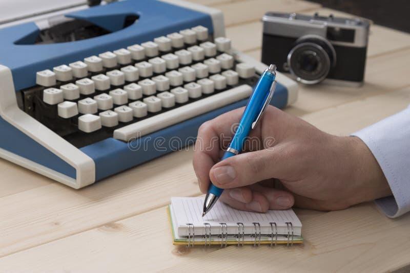 Journalista que toma notas na mesa imagem de stock