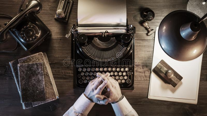 Journalista que trabalha em seu escrit?rio do vintage na noite foto de stock