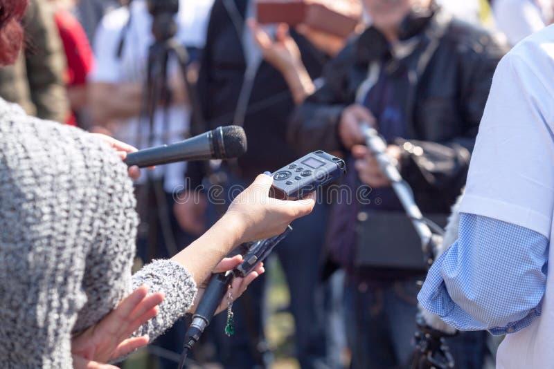 Journalistas que fazem a entrevista dos meios durante a conferência de imprensa fotografia de stock royalty free