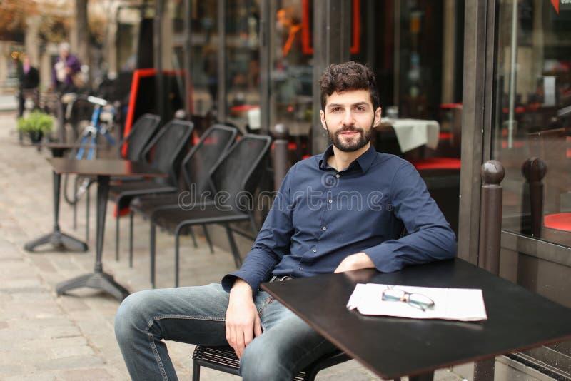 Journaliste avec la fin vers le haut de l'article de journal de lecture de visage au café images stock