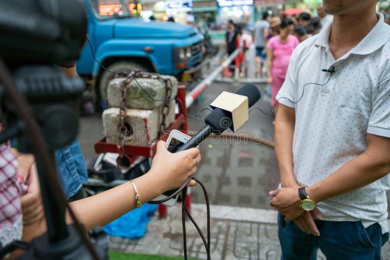 Journaliste avec microphone interviewé dans la rue photo stock