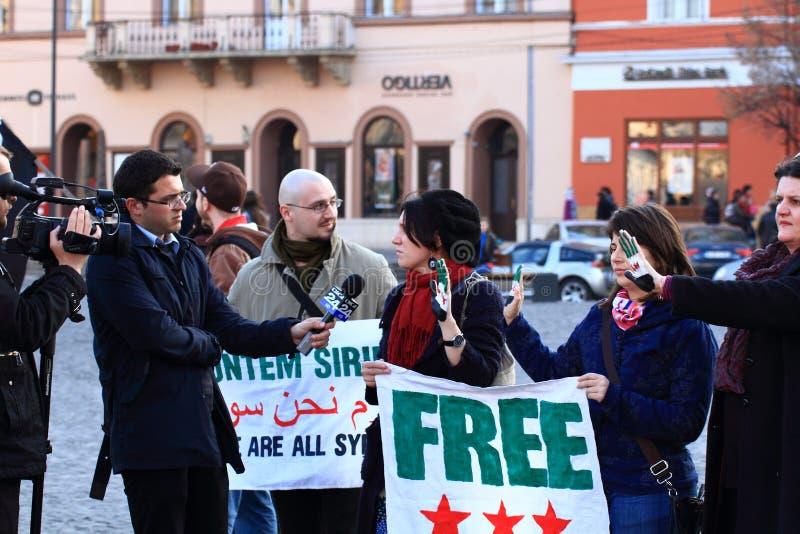Journaliste de TV interviewant un Syrien manifestant photographie stock libre de droits