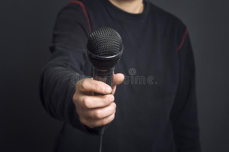 Journaliste faisant le discours avec le microphone et la main faisant des gestes le concept pour l'entrevue image libre de droits
