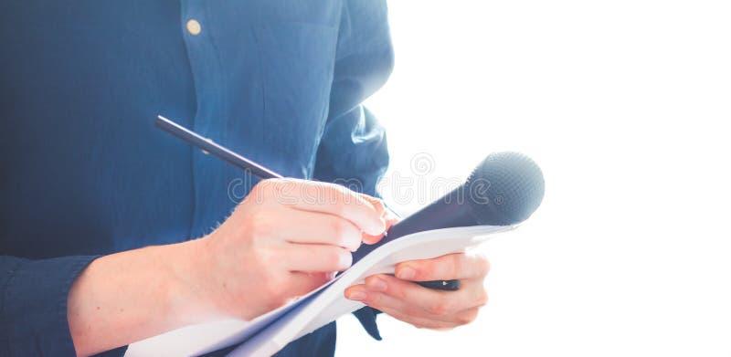 Journaliste masculin à la conférence de presse, tenant le microphone et prenant des notes photos stock