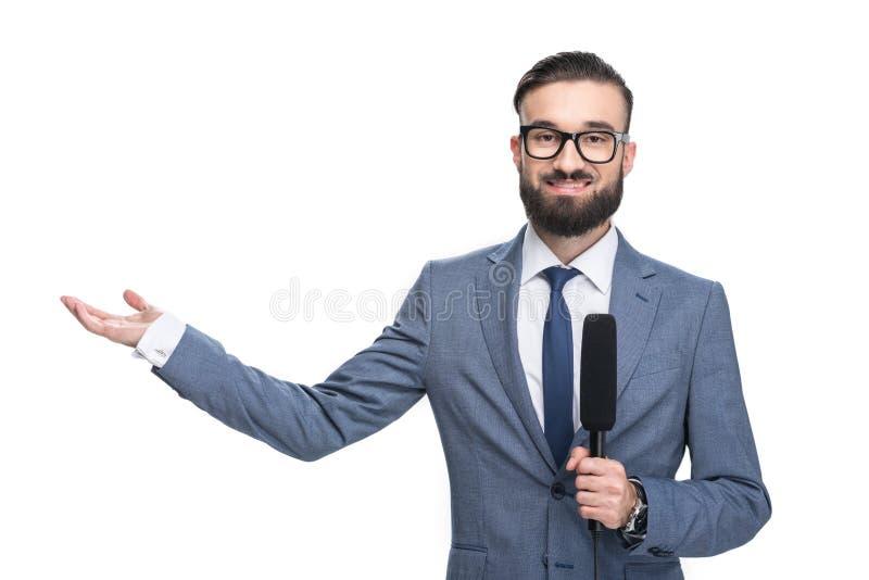 journaliste masculin de sourire beau avec le microphone présentant quelque chose, image libre de droits