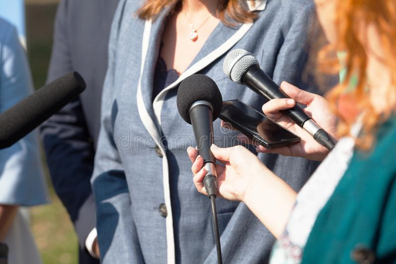 Journalists making media interview with businesswoman or female politician. Reporters making media interview with business woman or female politician royalty free stock photo