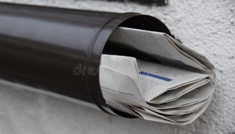 Journaux dans une boîte aux lettres photos stock