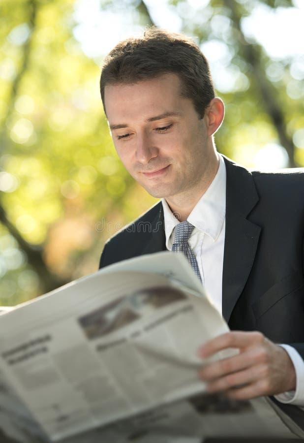 Journaux du relevé d'homme d'affaires image stock