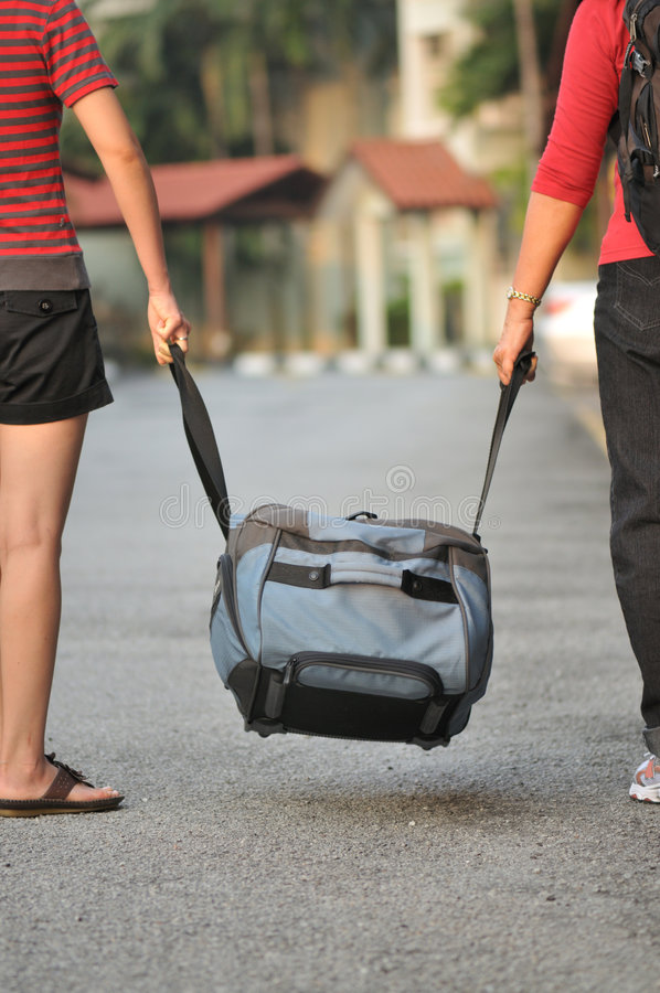 On a journey. A daughter helping her mother with her baggage stock photo