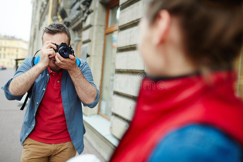 Journey shooting. Young men with photocamera shooting his girlfriend on tour royalty free stock image