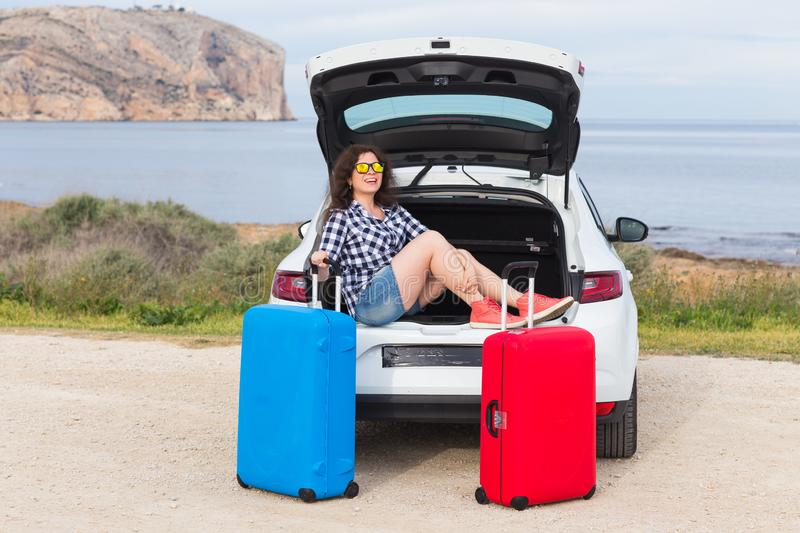 Journey, vacation, holiday and people concept - happy laughing woman going to travel by car with two huge suitcases stock image
