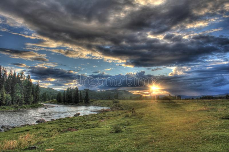 Journey through the wild nature of the Altai. Sunset in the valley of the mountain river Bashkaus. stock image