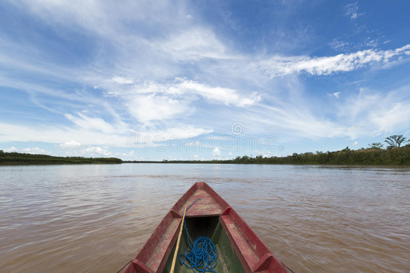 Journey on a wooden boat on Beni river near Rurrenabaque, blue s. Traveling on a wooden boat on Beni river in Bolivian jungle near Rurrenabaque with blue sky in stock photos