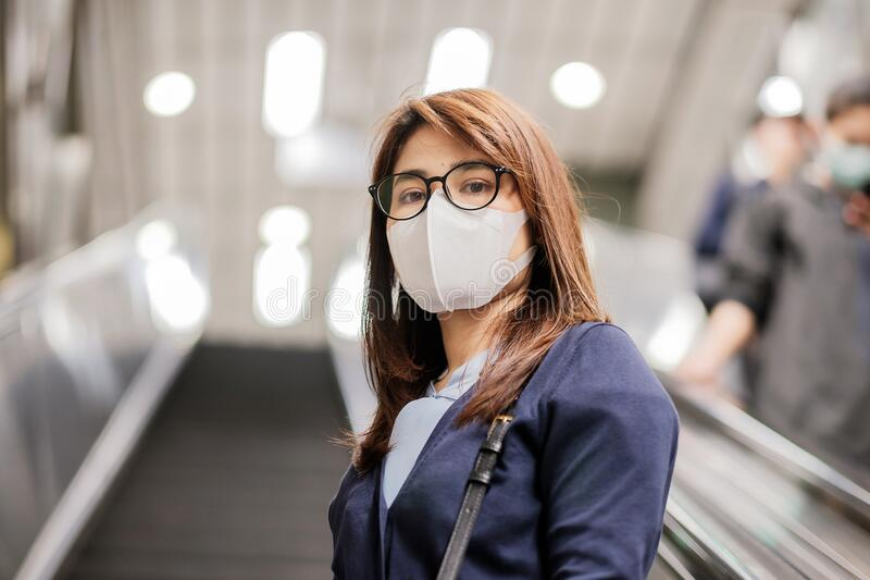 A jovem asiática que usa máscara de proteção contra o vírus da febre catarral ou da doença de Corona Covid- 19 no aeroporto é con foto de stock royalty free
