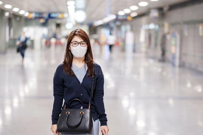 A jovem asiática que usa máscara de proteção contra o vírus da febre catarral ou da doença de Corona Covid- 19 no aeroporto é con fotografia de stock royalty free